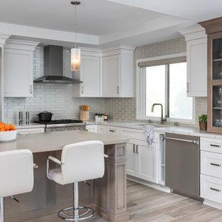Idéer för att renovera ett vintage flerfärgad flerfärgat kök, med en undermonterad diskho, skåp i shakerstil, vita skåp, beige stänkskydd, stänkskydd i glaskakel, rostfria vitvaror, mellanmörkt trägolv, en köksö och brunt golv