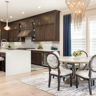 Design ideas for a mid-sized transitional l-shaped eat-in kitchen in Orange County with a farmhouse sink, shaker cabinets, dark wood cabinets, quartz benchtops, white splashback, glass tile splashback, stainless steel appliances, light hardwood floors, with island, brown floor and white benchtop.