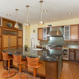 Exemple d'une cuisine exotique avec un placard à porte shaker, des portes de placard en bois brun, un plan de travail en granite, une crédence multicolore, une crédence en carreau briquette et un électroménager en acier inoxydable.