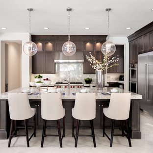Inspiration for a transitional l-shaped kitchen in Orange County with dark wood cabinets, stainless steel appliances, with island, beige floor, shaker cabinets, beige splashback, stone slab splashback, beige benchtop and marble floors.