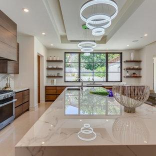 Ispirazione per una cucina ad ambiente unico moderna di medie dimensioni con ante marroni, paraspruzzi in lastra di pietra, elettrodomestici in acciaio inossidabile, pavimento in pietra calcarea e isola