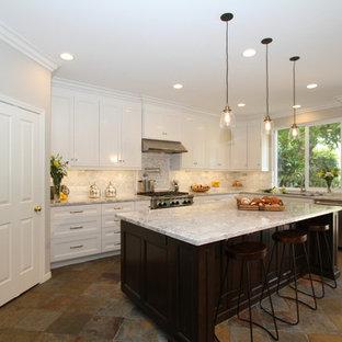Inredning av ett stort kök, med en undermonterad diskho, luckor med infälld panel, vita skåp, grått stänkskydd, stänkskydd i tunnelbanekakel, rostfria vitvaror, skiffergolv, en köksö och bänkskiva i kvarts
