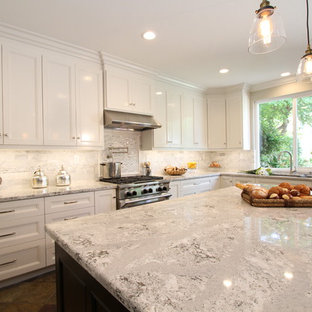 Large eat-in kitchen remodeling - Example of a large u-shaped slate floor eat-in kitchen design in Orange County with an undermount sink, recessed-panel cabinets, white cabinets, gray backsplash, subway tile backsplash, stainless steel appliances, an island and quartz countertops