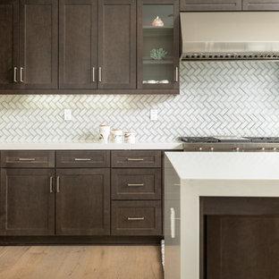 オレンジカウンティの中くらいのトランジショナルスタイルのおしゃれなキッチン (シェーカースタイル扉のキャビネット、濃色木目調キャビネット、クオーツストーンカウンター、白いキッチンパネル、ガラスタイルのキッチンパネル、シルバーの調理設備、淡色無垢フローリング、茶色い床、白いキッチンカウンター) の写真