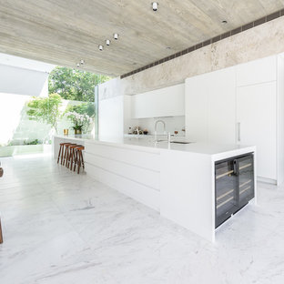 This is an example of an expansive contemporary galley open plan kitchen in Melbourne with flat-panel cabinets, white cabinets, solid surface benchtops, white splashback, panelled appliances, marble floors and with island.