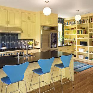 ポートランドの大きい北欧スタイルのおしゃれなキッチン (エプロンフロントシンク、ガラス扉のキャビネット、黄色いキャビネット、御影石カウンター、青いキッチンパネル、セラミックタイルのキッチンパネル、シルバーの調理設備の、無垢フローリング、黒いキッチンカウンター) の写真