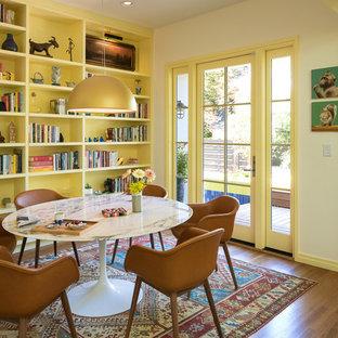 Große Stilmix Wohnküche mit Landhausspüle, Glasfronten, gelben Schränken, Granit-Arbeitsplatte, Küchenrückwand in Blau, Rückwand aus Keramikfliesen, Küchengeräten aus Edelstahl, braunem Holzboden, Kücheninsel und schwarzer Arbeitsplatte in Portland