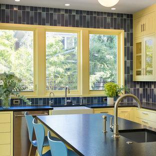 ポートランドの広い北欧スタイルのおしゃれなキッチン (エプロンフロントシンク、ガラス扉のキャビネット、黄色いキャビネット、御影石カウンター、青いキッチンパネル、セラミックタイルのキッチンパネル、シルバーの調理設備、淡色無垢フローリング、黒いキッチンカウンター) の写真