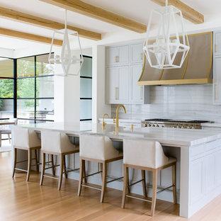 ダラスの巨大な地中海スタイルのおしゃれなキッチン (青いキャビネット、石スラブのキッチンパネル、淡色無垢フローリング、シェーカースタイル扉のキャビネット、グレーのキッチンパネル、シルバーの調理設備、ベージュの床、グレーのキッチンカウンター) の写真