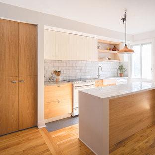 Zweizeilige, Mittelgroße Moderne Wohnküche mit Waschbecken, flächenbündigen Schrankfronten, hellbraunen Holzschränken, Arbeitsplatte aus Fliesen, Küchenrückwand in Weiß, Rückwand aus Keramikfliesen, weißen Elektrogeräten, Keramikboden, Kücheninsel und grauem Boden in Montreal