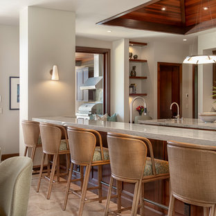 Tropical kitchen pictures - Example of an island style travertine floor and beige floor kitchen design in Hawaii with shaker cabinets, medium tone wood cabinets, quartzite countertops and porcelain backsplash