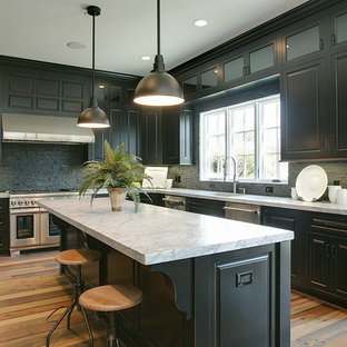 Large arts and crafts u-shaped open plan kitchen in DC Metro with an undermount sink, raised-panel cabinets, black cabinets, marble benchtops, black splashback, stone tile splashback, stainless steel appliances, medium hardwood floors and with island.