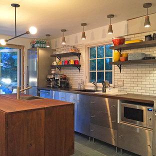 Imagen de cocina lineal, minimalista, con puertas de armario en acero inoxidable, encimera de madera, electrodomésticos de acero inoxidable, suelo de pizarra, una isla y encimeras marrones