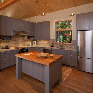 This is an example of a mid-sized country u-shaped eat-in kitchen in Seattle with an undermount sink, louvered cabinets, grey cabinets, granite benchtops, beige splashback, matchstick tile splashback, stainless steel appliances, medium hardwood floors and with island.