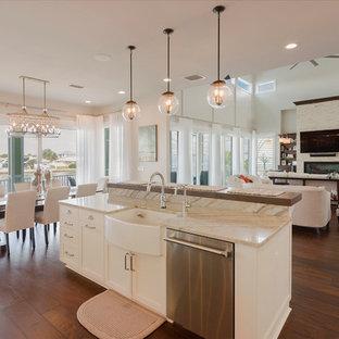 タンパの中くらいのトランジショナルスタイルのおしゃれなキッチン (エプロンフロントシンク、落し込みパネル扉のキャビネット、白いキャビネット、クオーツストーンカウンター、マルチカラーのキッチンパネル、ミラータイルのキッチンパネル、シルバーの調理設備、濃色無垢フローリング、茶色い床) の写真