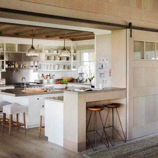 ボストンの大きいカントリー風おしゃれなキッチン (オープンシェルフ、白いキャビネット、メタリックのキッチンパネル、シルバーの調理設備、淡色無垢フローリング、エプロンフロントシンク、コンクリートカウンター、メタルタイルのキッチンパネル、茶色い床、グレーのキッチンカウンター) の写真