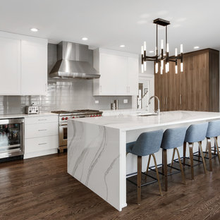 Inspiration för avskilda, stora moderna vitt l-kök, med en undermonterad diskho, släta luckor, vita skåp, bänkskiva i kvarts, grått stänkskydd, stänkskydd i glaskakel, integrerade vitvaror, en köksö, brunt golv och mörkt trägolv