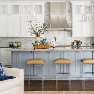 Offene, Große Klassische Küche in L-Form mit weißen Schränken, Küchenrückwand in Weiß, dunklem Holzboden, Kücheninsel, braunem Boden, grauer Arbeitsplatte, Unterbauwaschbecken, Schrankfronten mit vertiefter Füllung und Rückwand aus Marmor in Houston