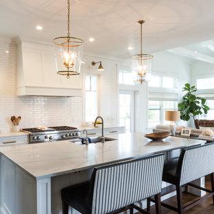 Idee per una cucina chic con lavello sottopiano, ante in stile shaker, ante bianche, paraspruzzi bianco, paraspruzzi con piastrelle diamantate, parquet scuro, isola, pavimento marrone e top bianco
