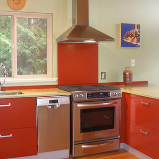 This is an example of a mid-sized contemporary open plan kitchen in Vancouver with flat-panel cabinets, red cabinets, recycled glass benchtops, red splashback, metal splashback and light hardwood floors.