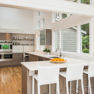 Contemporary kitchen photos - Example of a trendy u-shaped kitchen design in Seattle with a drop-in sink, flat-panel cabinets, dark wood cabinets and stainless steel appliances