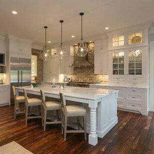 チャールストンの大きいトランジショナルスタイルのおしゃれなキッチン (濃色無垢フローリング、茶色い床、アンダーカウンターシンク、インセット扉のキャビネット、白いキャビネット、珪岩カウンター、赤いキッチンパネル、レンガのキッチンパネル、シルバーの調理設備の) の写真
