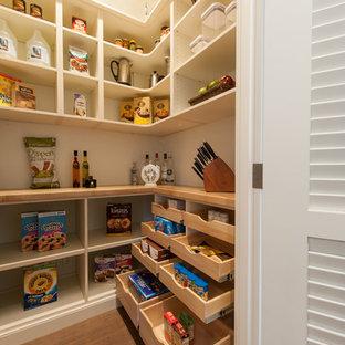 Klassisk inredning av ett stort kök, med en undermonterad diskho, skåp i shakerstil, vita skåp, bänkskiva i täljsten, blått stänkskydd, glaspanel som stänkskydd, integrerade vitvaror, bambugolv och en köksö