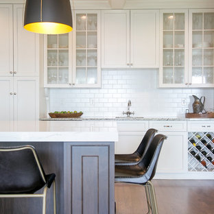Large transitional kitchen inspiration - Large transitional medium tone wood floor and brown floor kitchen photo in Milwaukee with a farmhouse sink, quartz countertops, white backsplash, subway tile backsplash, stainless steel appliances, an island, white countertops, shaker cabinets and white cabinets