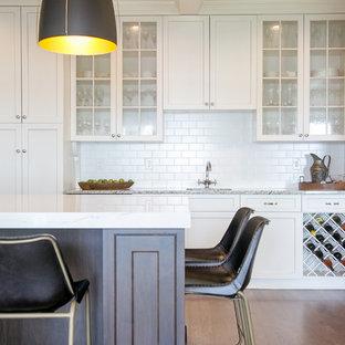 Geschlossene, Große Klassische Küche in U-Form mit Landhausspüle, Quarzwerkstein-Arbeitsplatte, Küchenrückwand in Weiß, Rückwand aus Metrofliesen, Küchengeräten aus Edelstahl, braunem Holzboden, Kücheninsel, weißer Arbeitsplatte, Schrankfronten im Shaker-Stil, weißen Schränken und braunem Boden in Milwaukee