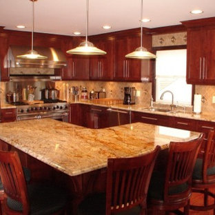オースティンの中サイズのトラディショナルスタイルのおしゃれなキッチン (アンダーカウンターシンク、フラットパネル扉のキャビネット、中間色木目調キャビネット、御影石カウンター、ベージュキッチンパネル、モザイクタイルのキッチンパネル、シルバーの調理設備の、濃色無垢フローリング) の写真