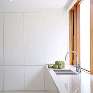 Contemporary kitchen in Brisbane with a double-bowl sink, flat-panel cabinets and white cabinets.