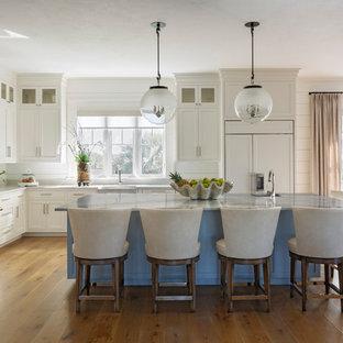 チャールストンのビーチスタイルのおしゃれなキッチン (エプロンフロントシンク、シェーカースタイル扉のキャビネット、白いキャビネット、青いキッチンパネル、サブウェイタイルのキッチンパネル、シルバーの調理設備の、無垢フローリング、グレーのキッチンカウンター) の写真