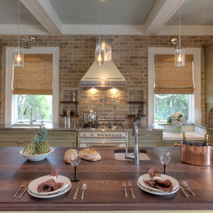 Photo of a large single-wall kitchen in Charleston with wood benchtops, stone tile splashback, white appliances, brown splashback, green cabinets, recessed-panel cabinets, an undermount sink and with island.