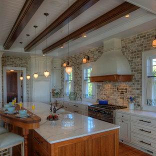 チャールストンのおしゃれなキッチン (大理石カウンター、シングルシンク、白いキャビネット、レンガのキッチンパネル、シルバーの調理設備の、茶色い床、白いキッチンカウンター) の写真
