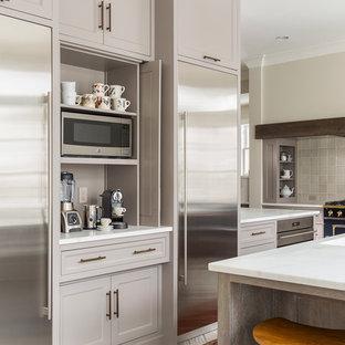 ミネアポリスの広いおしゃれなキッチン (アンダーカウンターシンク、落し込みパネル扉のキャビネット、グレーのキャビネット、大理石カウンター、グレーのキッチンパネル、セラミックタイルのキッチンパネル、磁器タイルの床、シルバーの調理設備) の写真