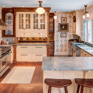 This is an example of a traditional u-shaped kitchen in Portland Maine with a farmhouse sink, flat-panel cabinets, beige cabinets, beige splashback, stainless steel appliances and blue benchtop.