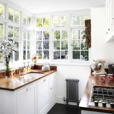 Example of a small classic galley kitchen design in London with an undermount sink, shaker cabinets, white cabinets, wood countertops and white backsplash