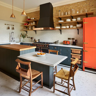 This is an example of a country l-shaped kitchen in London with a belfast sink, recessed-panel cabinets, green cabinets, wood worktops, white splashback, metro tiled splashback, black appliances, an island, white floors and brown worktops.