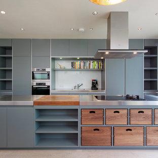 Große Moderne Küche mit integriertem Waschbecken, flächenbündigen Schrankfronten, grauen Schränken, Edelstahl-Arbeitsplatte, Küchenrückwand in Weiß, Glasrückwand, Küchengeräten aus Edelstahl und Kücheninsel in London