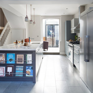 Large traditional galley open plan kitchen in London with an integrated sink, grey cabinets, solid surface benchtops, grey splashback, subway tile splashback, stainless steel appliances and with island.