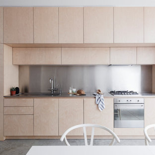 Design ideas for a modern single-wall kitchen/diner in London with an integrated sink, flat-panel cabinets, light wood cabinets, metallic splashback, metal splashback, stainless steel appliances, concrete flooring, no island, grey floors and grey worktops.