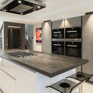 This is an example of a medium sized contemporary kitchen in London with flat-panel cabinets, stainless steel appliances, an island, beige floors, black worktops and grey cabinets.