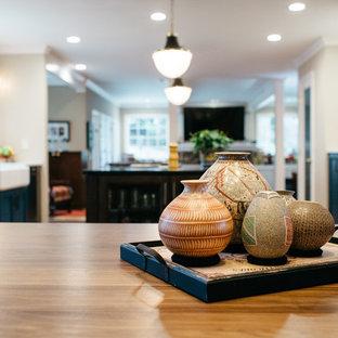 シアトルの中くらいのトランジショナルスタイルのおしゃれなキッチン (エプロンフロントシンク、落し込みパネル扉のキャビネット、茶色いキャビネット、珪岩カウンター、グレーのキッチンパネル、磁器タイルのキッチンパネル、シルバーの調理設備、無垢フローリング、赤い床、黒いキッチンカウンター) の写真