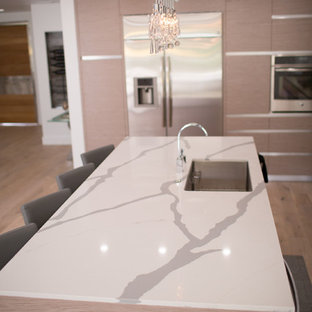 Inspiration for a mid-sized modern single-wall open plan kitchen in Seattle with a double-bowl sink, open cabinets, white cabinets, quartzite benchtops, grey splashback, marble splashback, stainless steel appliances, bamboo floors, with island and brown floor.