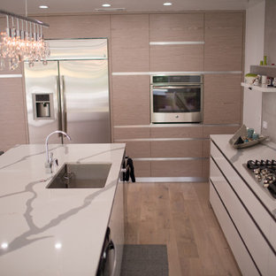 Photo of a mid-sized modern single-wall open plan kitchen in Seattle with a double-bowl sink, open cabinets, white cabinets, quartzite benchtops, grey splashback, marble splashback, stainless steel appliances, bamboo floors, with island and brown floor.