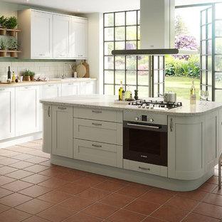 Inredning av ett klassiskt stort linjärt kök och matrum, med vitt stänkskydd, stänkskydd i tunnelbanekakel, rostfria vitvaror, klinkergolv i terrakotta och en köksö