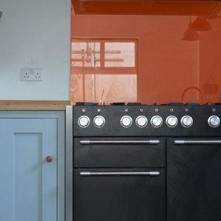 Ispirazione per una cucina american style di medie dimensioni con ante in stile shaker, ante turchesi, top in legno, paraspruzzi arancione, paraspruzzi con lastra di vetro, elettrodomestici neri, parquet scuro e isola