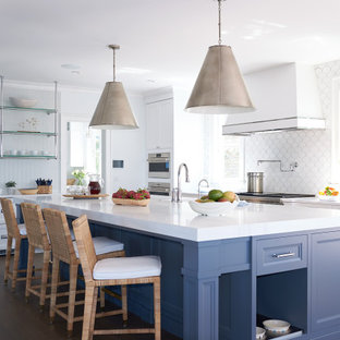 This is an example of a large beach style u-shaped kitchen/diner in New York with a belfast sink, recessed-panel cabinets, blue cabinets, engineered stone countertops, white splashback, ceramic splashback, stainless steel appliances, dark hardwood flooring, an island, brown floors and white worktops.