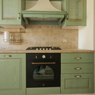 ミラノの中サイズのカントリー風おしゃれなキッチン (ダブルシンク、レイズドパネル扉のキャビネット、緑のキャビネット、タイルカウンター、ベージュキッチンパネル、セラミックタイルのキッチンパネル、黒い調理設備、磁器タイルの床、アイランドなし) の写真