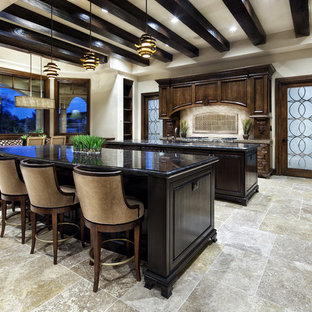 Inspiration for a mediterranean kitchen in Dallas with raised-panel cabinets, dark wood cabinets and black worktops.